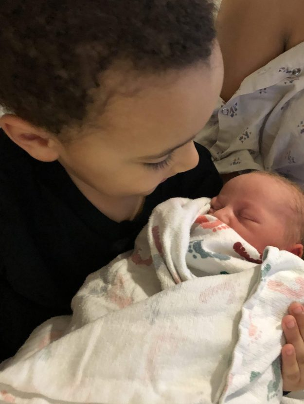 Son holding baby sibling